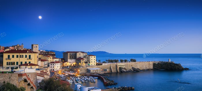Piombino old town twilight panoramic view on piazza bovio lighth