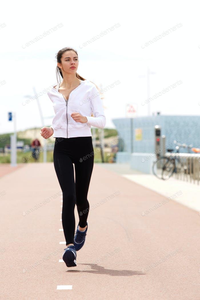 Young woman runner on path outside