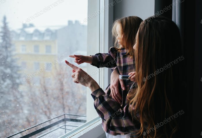 Mom with little girl looking through the window