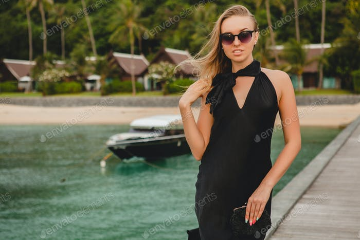 luxury sexy attractive woman dressed in romantic black dress posing on pier in luxury resort hotel