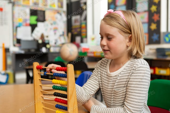 Side view of a Caucasian schoolgirl learning mathematics with an abacus in the classroom at school
