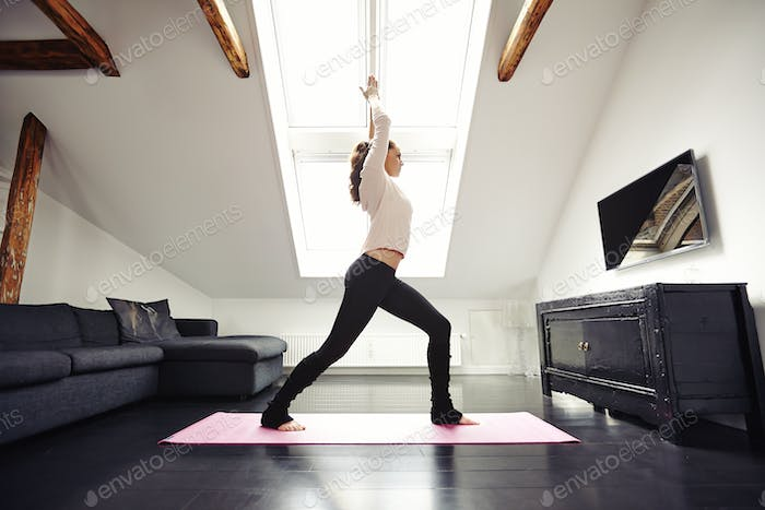 Fit woman practicing yoga in living room