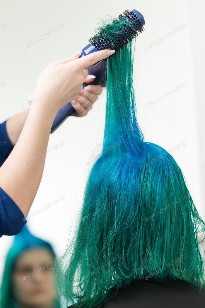 Hairdresser Combs and Dries Hair of Emerald Color with Hairdryer After Dyeing Hair Roots