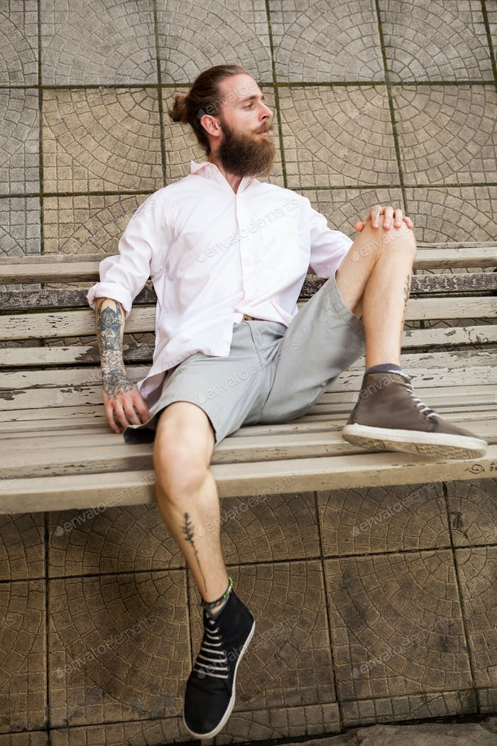 Bearded hipster lying on a bench