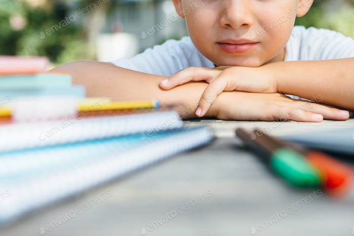 Crop child at table with school supplies