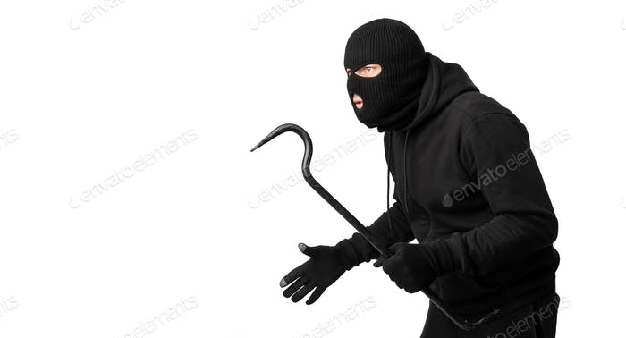 Thief wearing black mask and hoodie looking at copyspace