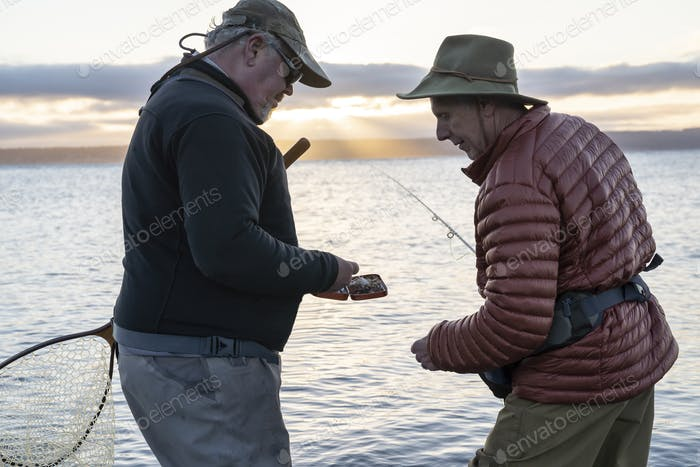 A male fly fisherman watches his guide work putting on a new fly to try for salmon or trout at a