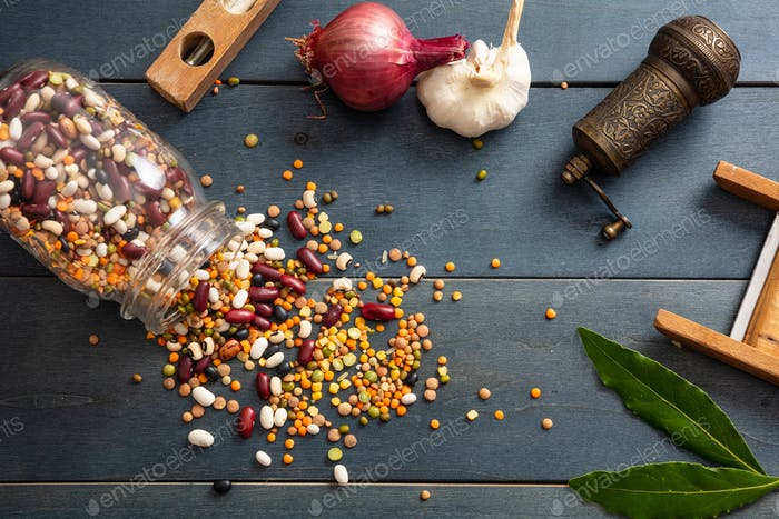 Close up of assortment of legumes in a glass jar, spilled on a wooden tabletop background