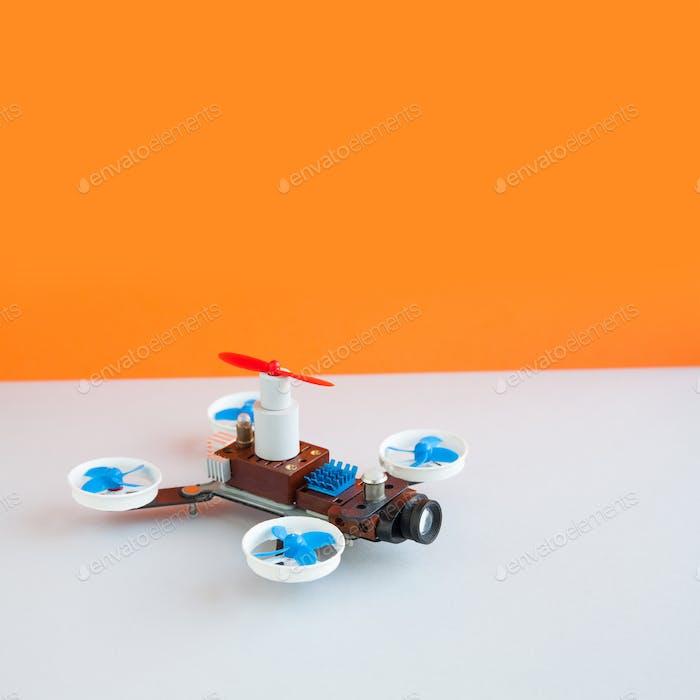 Drone multicopter with camera, orange white background.