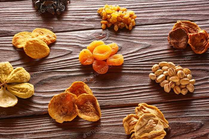 Dried fruits and nuts on wooden background