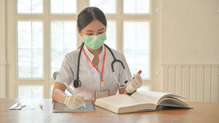 Nurses wear gloves and mask use tablet to record blood test results for covid-19 virus infected.