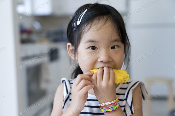 Happy little girl eating mango