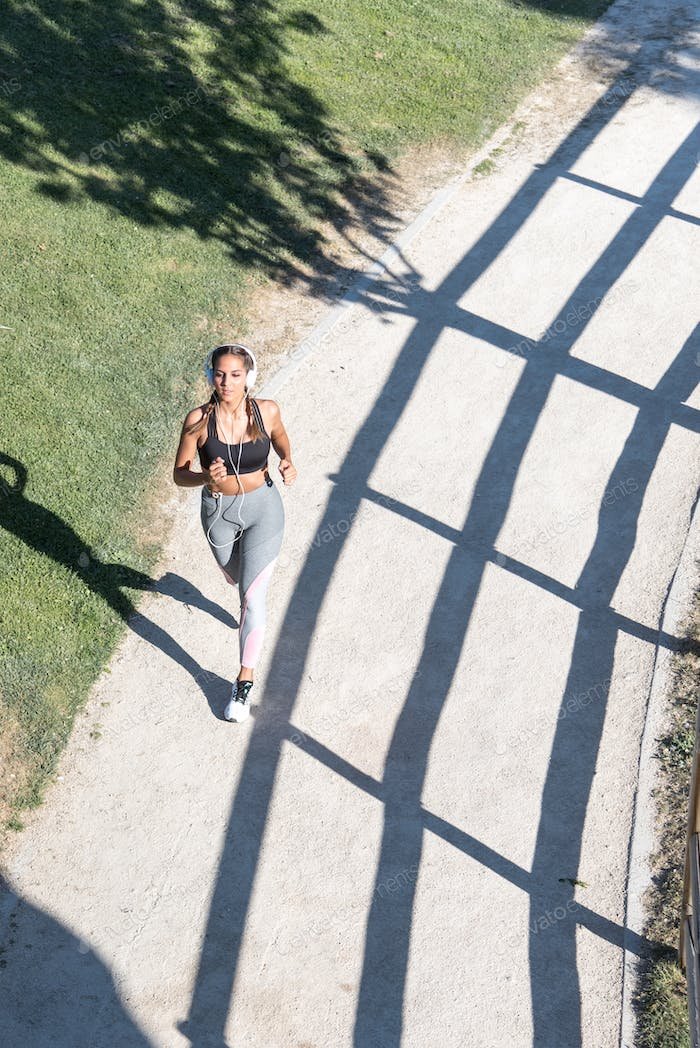 young Woman running jogging in a park outdoors listening music