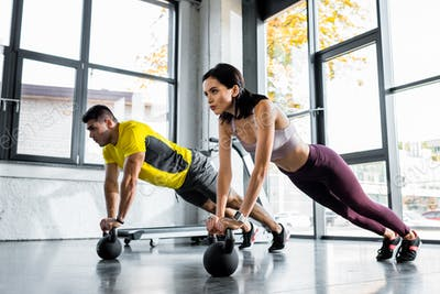 sportsman and sportswoman doing plank on weights in sports center