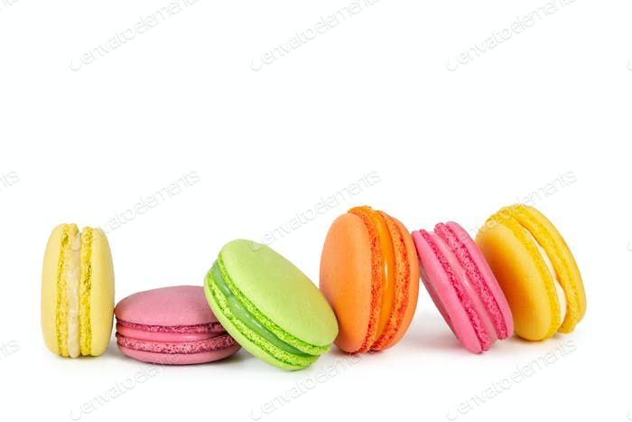Colorful french macaroons in row isolated on white