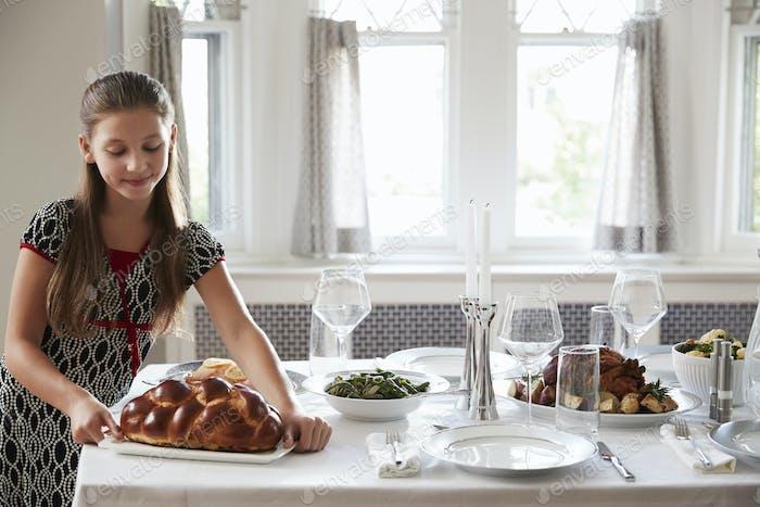 Mädchen Platzierung Challah Brot auf einem Tisch für Shabbat Mahlzeit