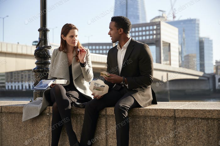 Two millennial colleagues take a break sitting on the embankment eating near London Bridge