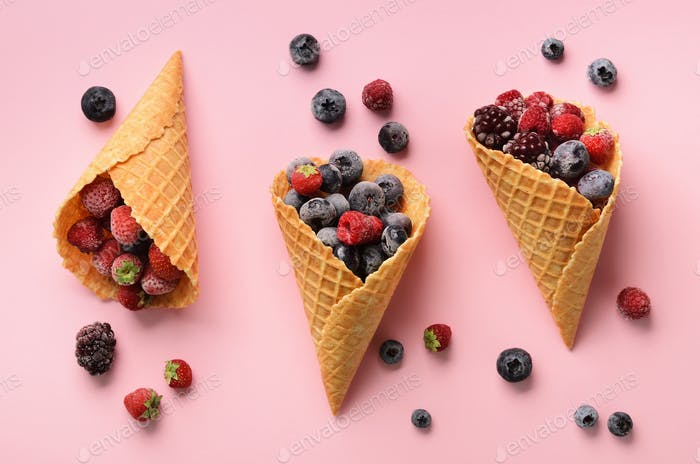 Frozen berries - strawberry, blueberry, blackberry, raspberry in waffle cones on pink background