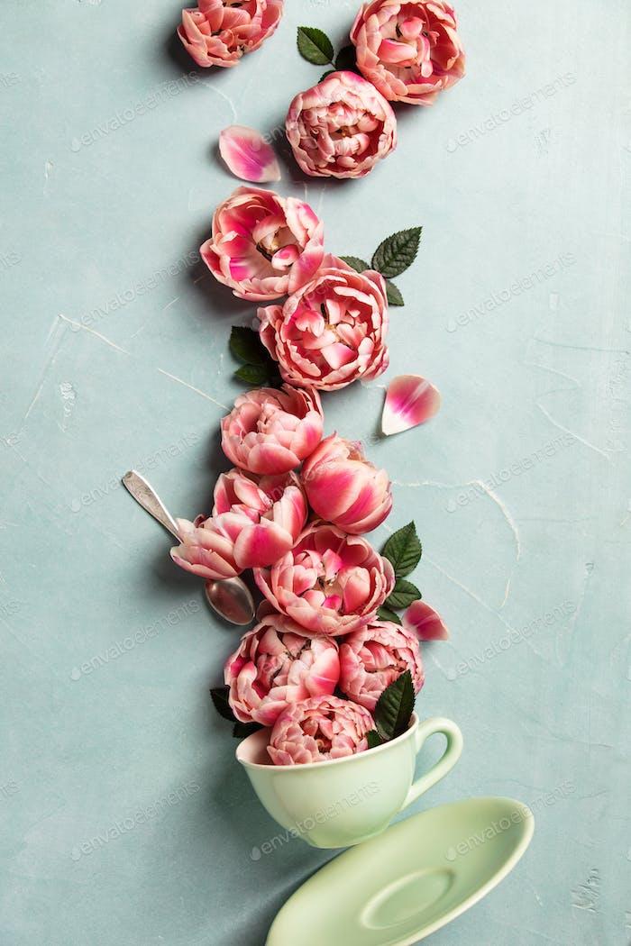 Kreatives Layout aus Kaffee oder Teetasse mit rosa Blumen auf blauem Hintergrund