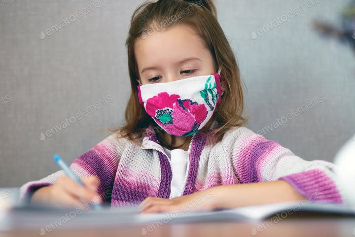 Schoolgirl girl in mask studying homework at home, social distance during quarantine coronavirus