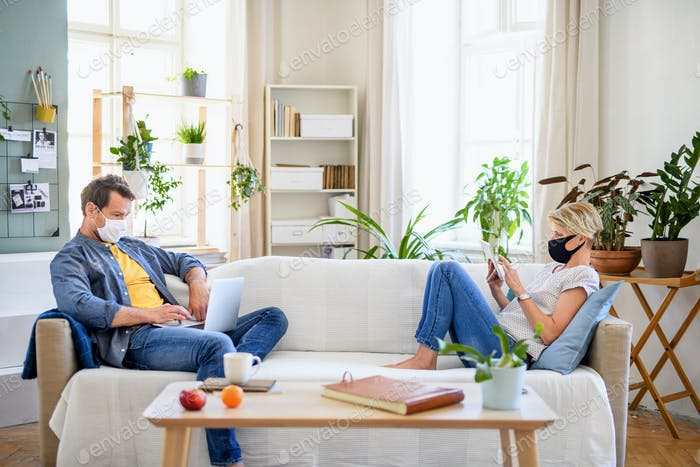 Couple with face masks sitting indoors at home, using technology