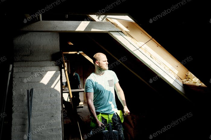 Человек работает, чтобы отремонтировать старый чердак