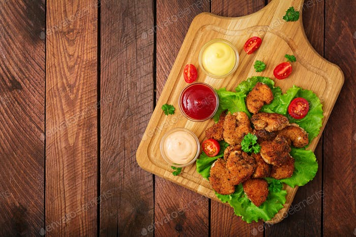 Chicken nuggets and sauce on a wooden background. Flay lay. Top view