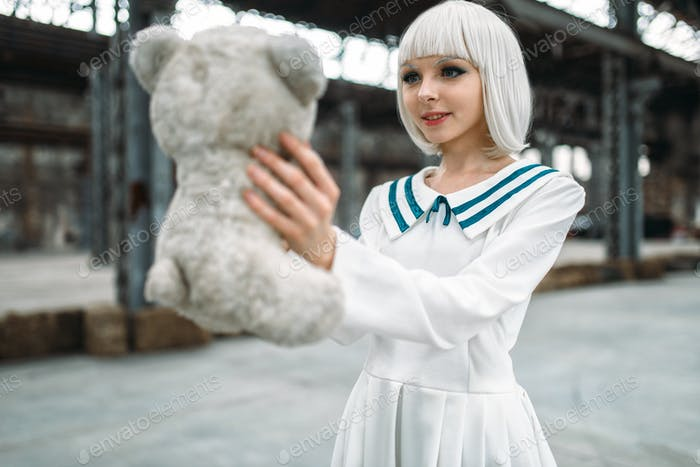 Anime style blonde woman looks at the toy bear