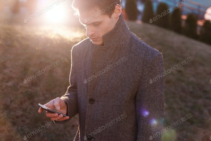 A handsome young businessman using his phone