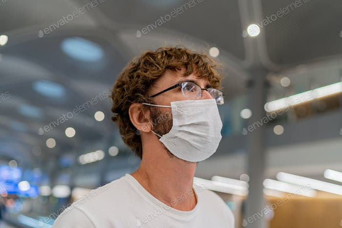 Traveler  man wearing face mask waiting to board info airplane