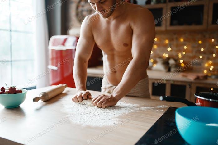 Muscular husband in underwear cooking on kitchen