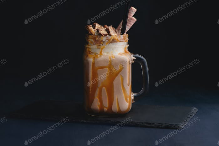 Cold chocolate and caramel milkshake in a vintage glass mason jar. Dark background with copy space