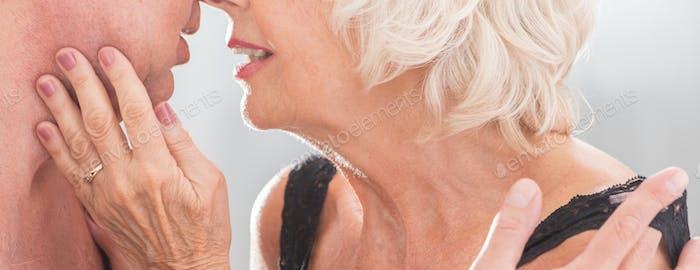 Elderly woman in lingerie kissing husband