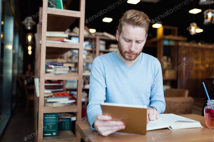 Young male student reading in coffee shop