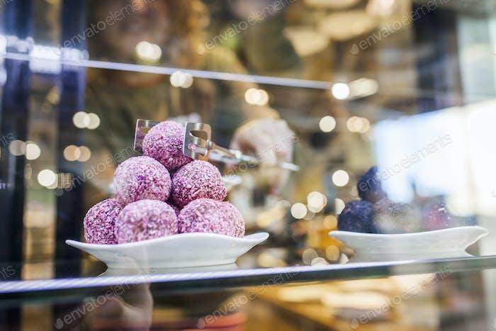 Defocused image of woman picking sweet food at supermarket