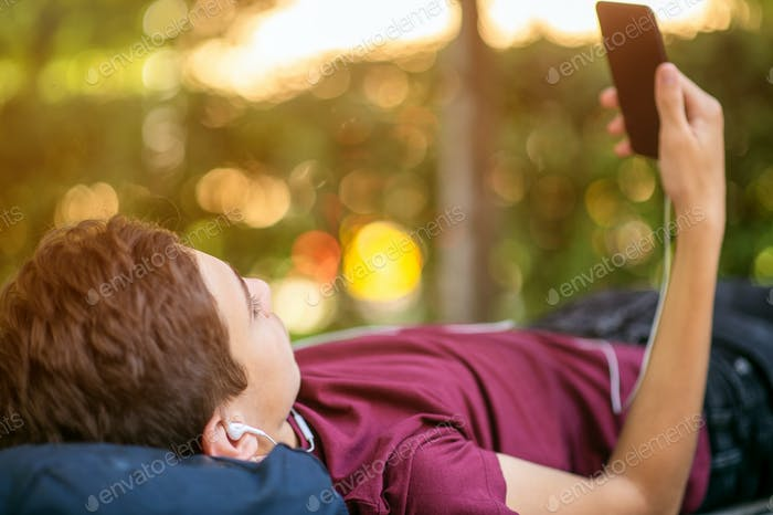 Teen boy with smartphone lies on the bench in the park.