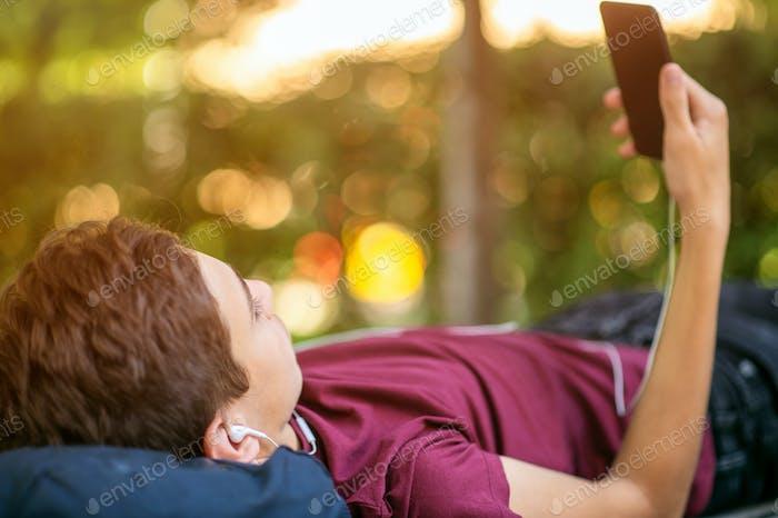 Teen Junge mit Smartphone liegt auf der Bank im Park.