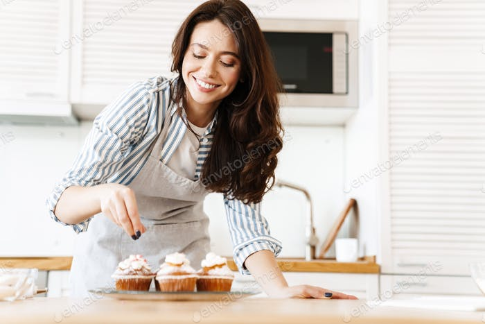 Image of caucasian happy woman smiling and cooking muffins