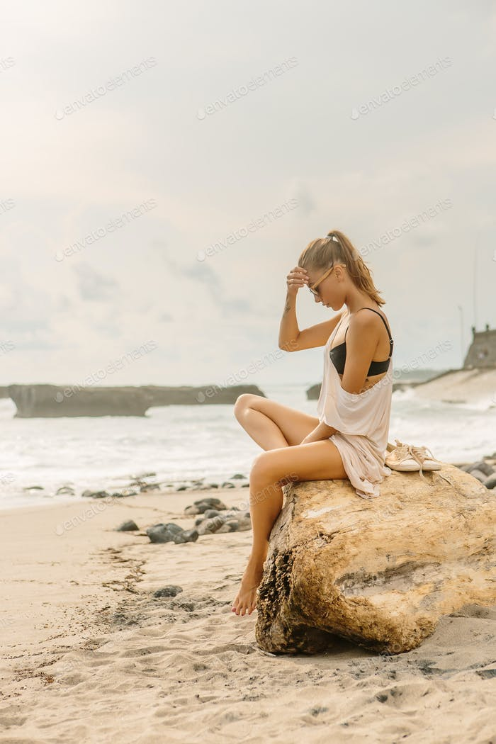 Pretty woman sit on big stone on ocean shore.