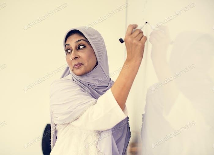 Muslim teacher writing on a white board