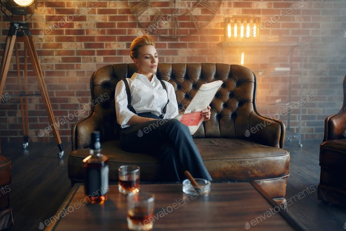 Woman reading newspapar with whiskey and cigar