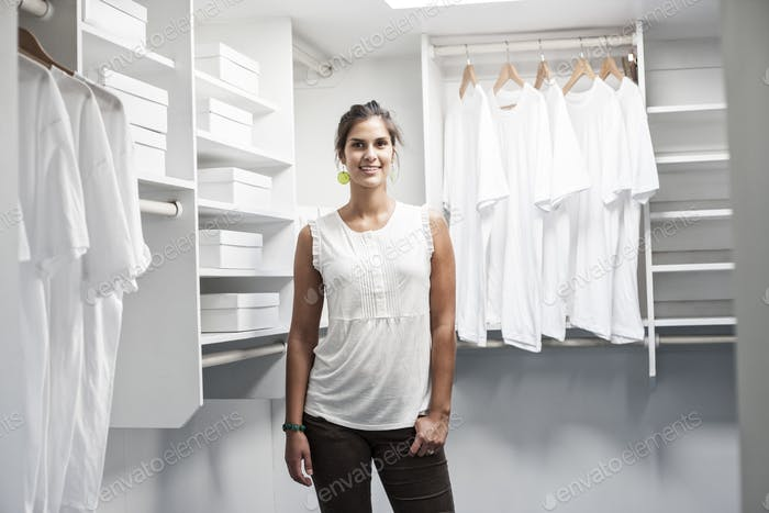 Portrait of HIspanic woman in a closet full of white clothes.