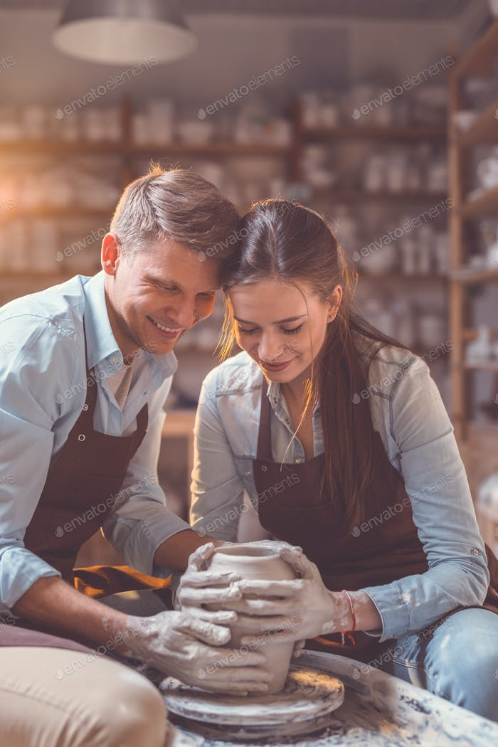 Smiling couple at the potter's wheel