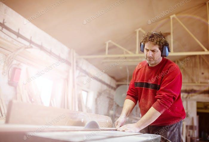 Carpenter sawing wooden planks
