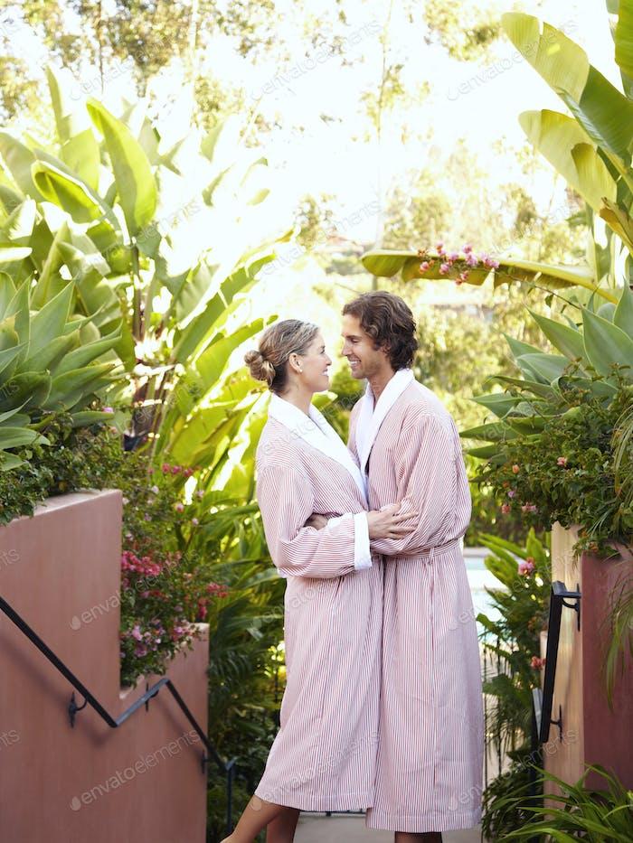 Caucasian couple in robes hugging