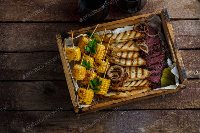 Grilled corn, sliced pastrami and toasted bread with wine, top view copy space