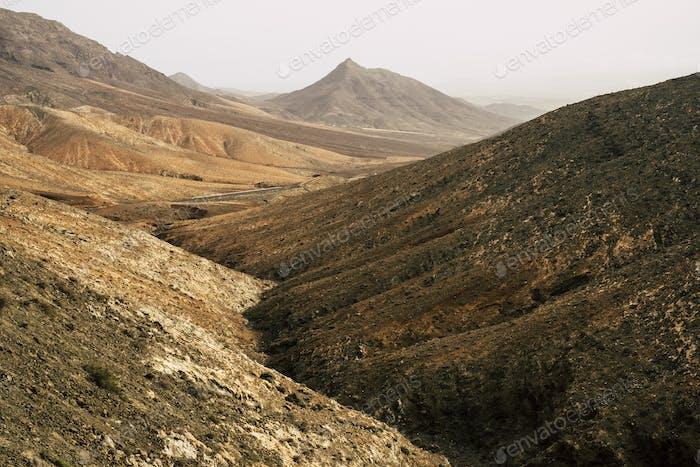 Paisaje salvaje dentro de la isla de Fuerteventura con altas montañas desérticas de vulcanos