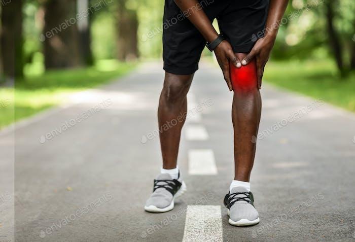 Beschnitten von schwarzem Sportler, der sein entzündetes Knie berührt