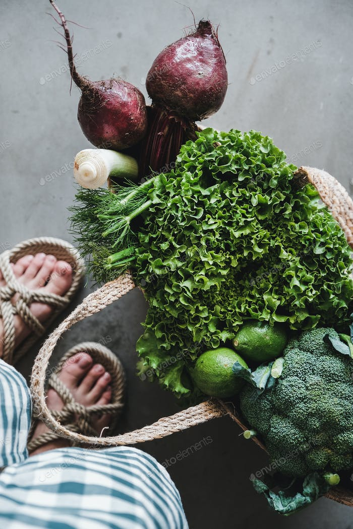 Jute grocery shopping bag full of fresh vegetables and greens