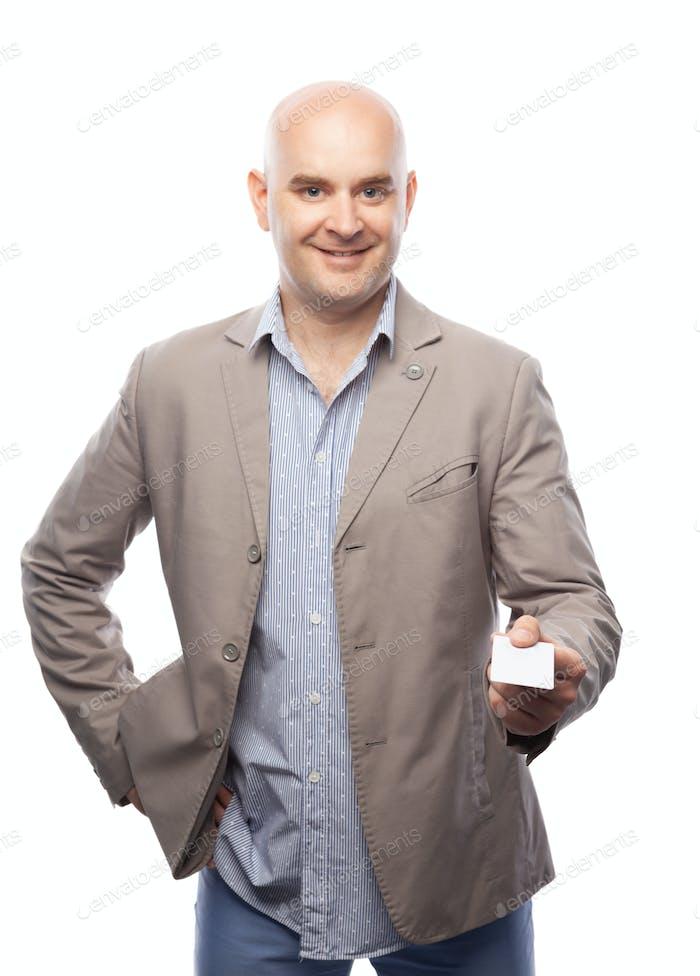 Ein kahler Mann in einem beige Anzug zeigt eine Visitenkarte isoliert auf weiß